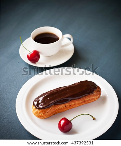 Delicious chocolate glazed french eclair filled with pastry cream, served with coffee and cherries. Close up view, Dark background. - stock photo