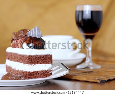 Delicious chocolate layer cake topped with cream and chocolate sauce and a glass of red wine - stock photo