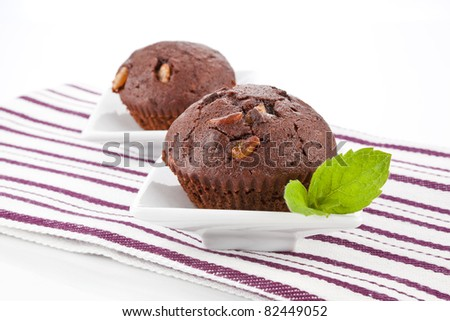 Delicious chocolate muffins with fresh mint on luxurious kitchen cloth. - stock photo