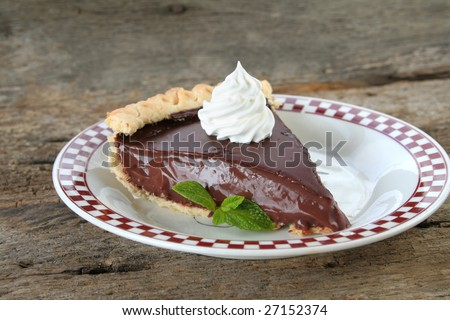 Delicious chocolate pie with whipped topping and a mint leaf for garnish. - stock photo