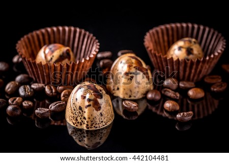 Delicious chocolate pralines on black background - stock photo