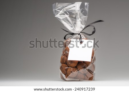 Delicious chocolate truffles bag isolated on grey background. Left copy space. Blank label that you can add your own trademark or your own message. Fun composition and lighting. Shooting in studio. - stock photo