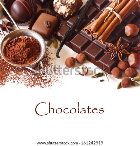 Delicious chocolates and spices on a white background. - stock photo