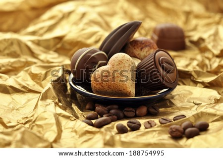 Delicious chocolates on a golden background - stock photo