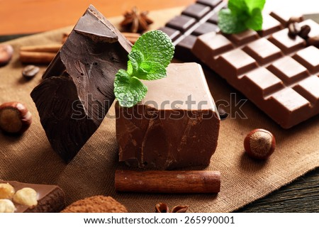 Delicious chocolates with spices on table, closeup - stock photo