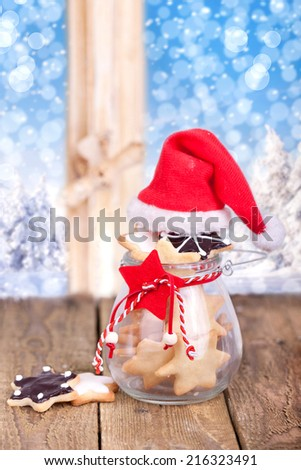 delicious christmas cookies in a glass and a red Santa Claus hat on rustic wooden table, in background a snow-covered winter wonderland (wood) with snowflakes  - stock photo