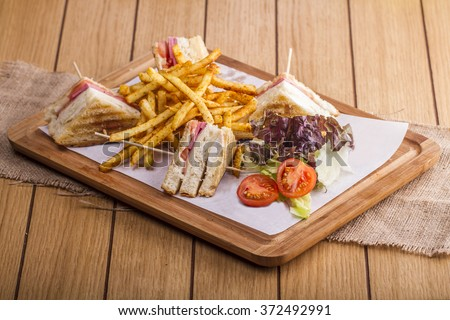 Delicious club sandwich with french fries, salad and tomato at a diner on wooden table background - stock photo