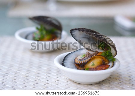 Delicious cockles cooked with lemon juice and parcley, baked and served on small plates as entree. Copy space - stock photo