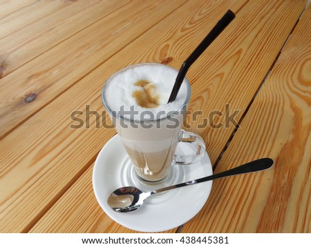 Delicious coffee latte with milk foam and a straw in a glass with handle.The glass stands on a white saucer on an unpainted wooden table.In the saucer lies a brilliant dessert spoon with long handle.  - stock photo