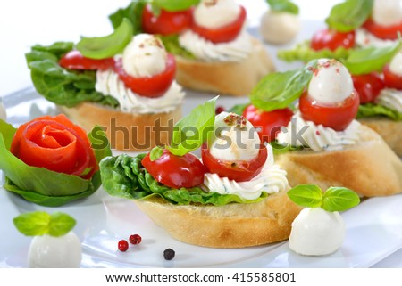Delicious cold starters: Slices of baguette with cherry tomatoes, mozzarella balls, cream cheese, olive oil and basil leaves  - stock photo