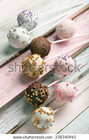 Delicious colorful cake pops on a wooden surface - stock photo