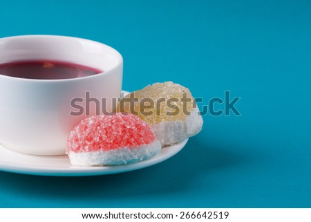 Delicious colorful marmalade with a cup of tea. Close-up of colorful candy marmelade on the plate. - stock photo