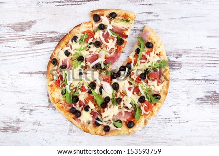 Delicious colorful round pizza on white wooden background, top view. Rustic style traditional delicious pizza eating. - stock photo