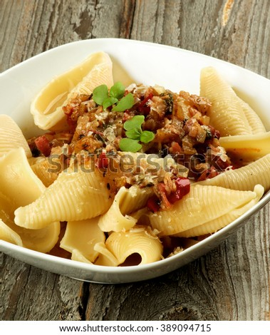Delicious Conchiglie Giganti Pasta (Giant Pasta Shells) with Meat Sauce Bolognese in White Bowl Cross Section on Wooden background