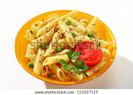 Delicious cooked tubular pasta dish / a portion of cooked macaroni noodles served with green parsley and tomato in an orange plate  - stock photo