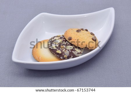 Delicious cookies and biscuits on white plate and gray background - stock photo