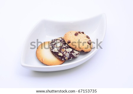 Delicious cookies and biscuits on white plate and white background - stock photo