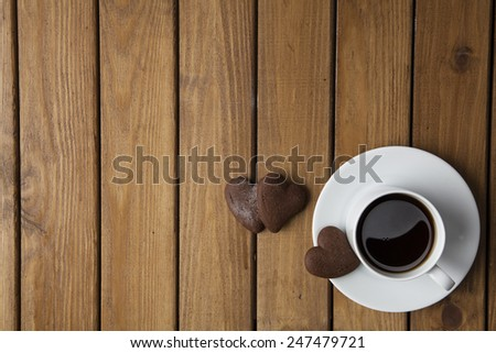 Delicious cookies and cup of coffeee on wooden background