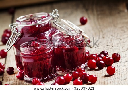 Delicious cranberry jam in glass jars and fresh cranberry on an old wooden background in rustic style, selective focus - stock photo