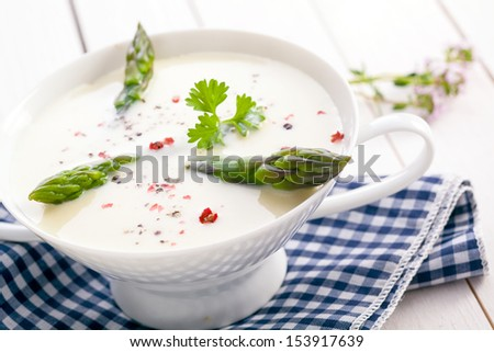 Delicious cream of asparagus soup with green asparagus shoots served in a dainty white bowl on a checkered cloth - stock photo