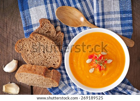 Delicious cream of pumpkin soup in a bowl on wooden table. Top view - stock photo
