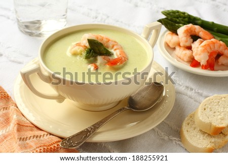 Delicious cream soup with asparagus and shrimp. Selective focus - stock photo