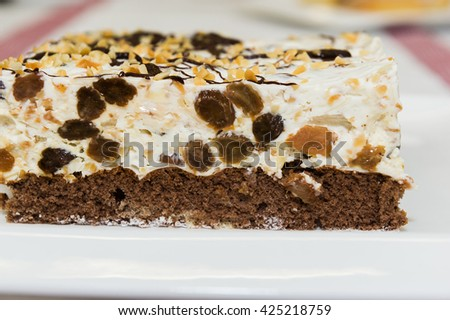 Delicious creamy cake with fruits, raisins and peanuts on top. - stock photo