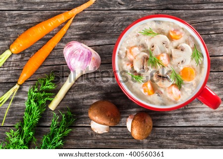 Delicious creamy cheese mushroom soup with spring carrots and veggies, decorated with dill, in a red cup on an old rustic table, top view - stock photo