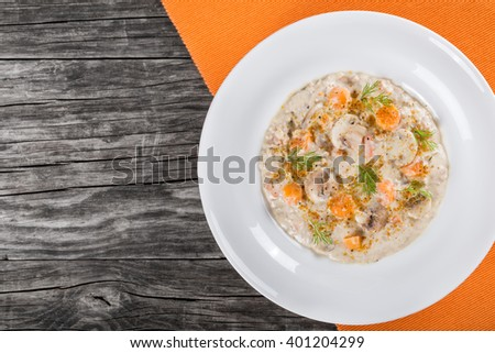 Delicious creamy cheese mushroom soup with spring carrots, ground meat and spices, decorated with dill, in a white wide rim dish on a cutting board on an old rustic table, horizontal top view - stock photo