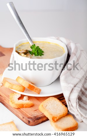 delicious creamy soup with croutons and greens on Boards - stock photo