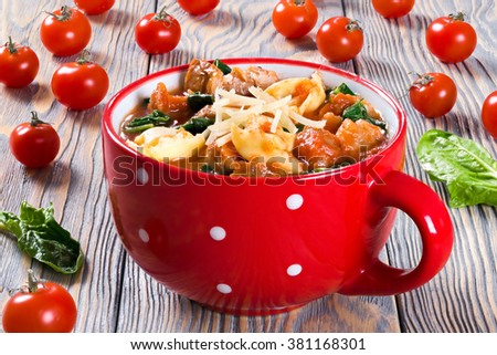Delicious creamy tomato soup with tortellini, Italian sausages, spinach, decorated with parmesan cheese in a red mug on a table, close-up, selective focus - stock photo