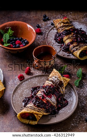 Delicious crepes with forest fruit, topped and filled with forest fruit, mint and dark chocolate, delicious breakfast - stock photo