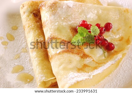 Delicious crepes with honey and berries - stock photo
