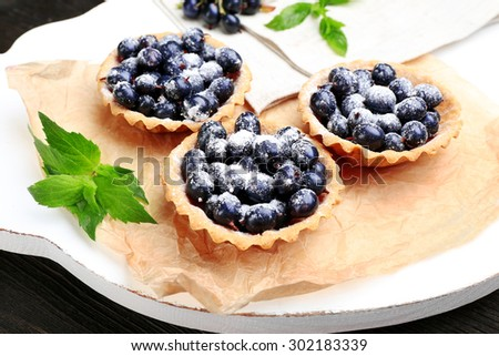 Delicious crispy tarts with black currants on parchment on wooden board, closeup - stock photo