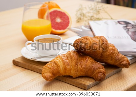 Delicious croissant with a cup of coffee and a glass of orange juice - stock photo