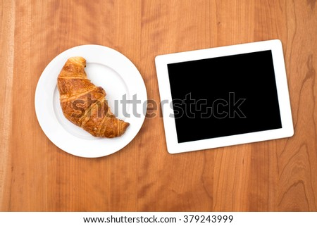 delicious croissant with tablet PC on wooden table from above - stock photo