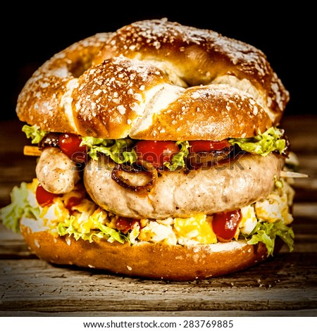 Delicious crusty burger with smoked German sausage, fresh salad ingredients and tomato ketchup, close up square view - stock photo