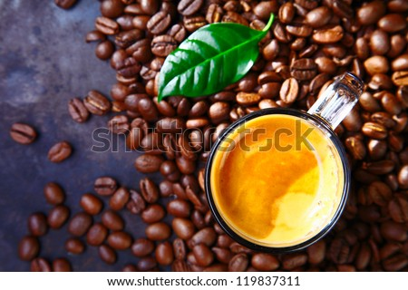 Delicious cup of coffee with beans and green coffe plant leaf - stock photo