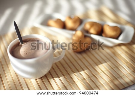 Delicious cup of hot chocolate and biscuits with heart shape - stock photo
