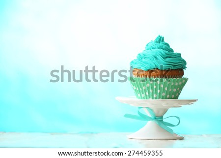 Delicious cupcake on blue background - stock photo