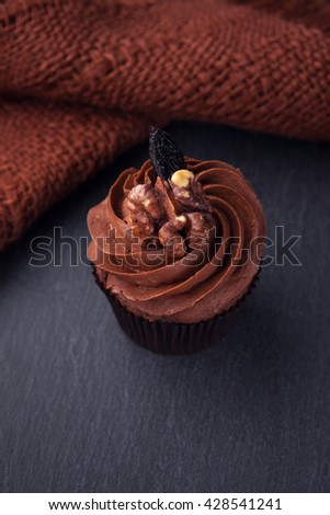 Delicious cupcake with chocolate cream on a black background