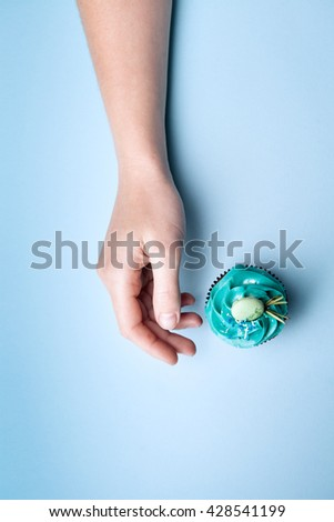 Delicious cupcake with cream and hand on a blue background