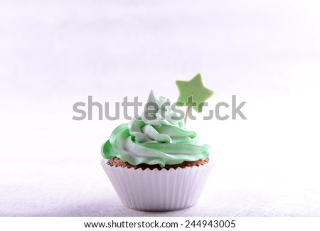 Delicious cupcake with inscription on table on beige background - stock photo