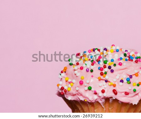 delicious cupcake with pink frosting and sprinkle decorations - stock photo