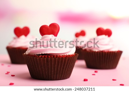 Delicious cupcakes for Valentine Day on bright background - stock photo