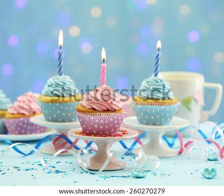 Delicious cupcakes on table on blue background