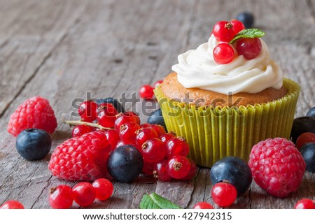 Delicious cupcakes with berries - stock photo