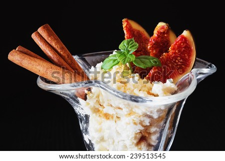 delicious curd dessert with sliced fruit, cinnamon and fresh mint leaves on a black background. close-up.health and diet food - stock photo