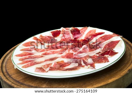 Delicious cured ham isolated on black background - stock photo