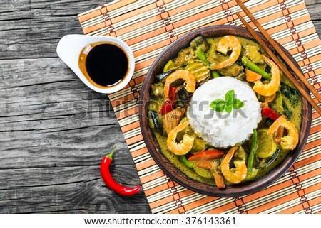 delicious curry with vegetables, rice and prawns on the brown clay dish with chopsticks on a white old wooden table with soy sauce in a gravy boat, top view, close-up - stock photo